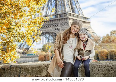 Mother And Child Tourists Sitting On The Parapet In Paris