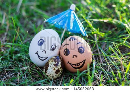 Funny eggs imitating happy smiling mixed couple white and colored parents with versicolored baby under umbrella