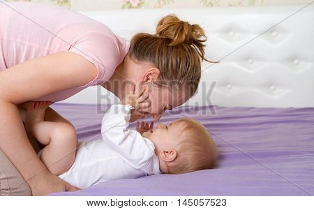 Mum plays with little girl on a bed