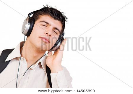 Portrait of young man listening music in headphones with great pleasure isolated on white background, space for text