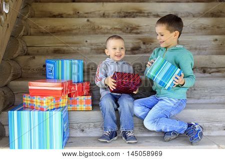 happy children received gifts. two boys happily smiling and holding gifts in hands. Children sitting on the wooden stairs. the concept of a family celebration with lots of gifts