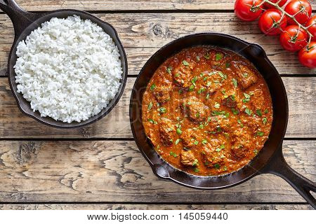 Beef Madras traditional slow cook Indian spicy chili lamb meat food with rice and tomatoes in cast iron pan on vintage wooden table background. India culture restaurant dish.