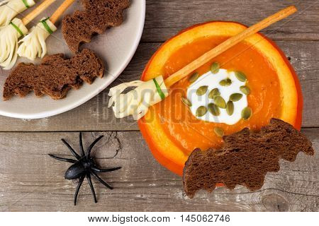 Halloween Pumpkin Soup With Witch's Broom And Bat Bread Snacks On A Rustic Wooden Background