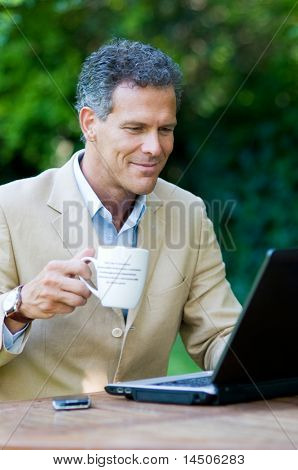 Satisfied businessman working on laptop outdoor while drinking a mug of coffee