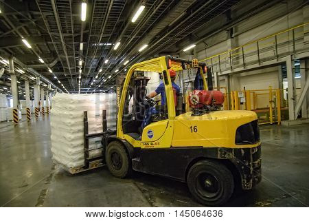 Tobolsk, Russia - July 15. 2016: Sibur company. Central control panel of Tobolsk Polymer plant. Driver on forklift truck loads pallets with finished goods from packaging machine to warehouse
