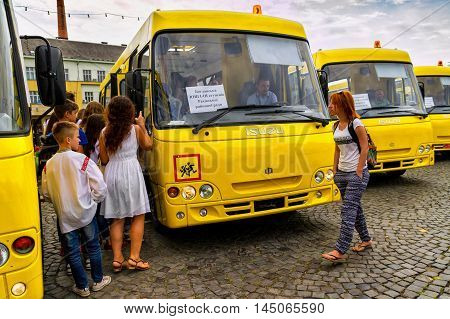 Students considering new school buses during their transmission to the representatives of educational institutions in four districts of the Transcarpathian region Uzhgorod August 30 2016