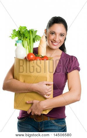 Young woman holding a grocery bag full of fresh and healthy food isolated on white background