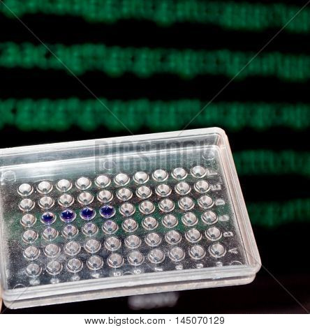 DNA testing in the laboratory. Well plate with samples on the background of the DNA sequence.