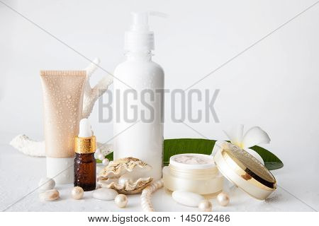 Nameless cosmetic containers(jar bottle and tube) and pearl in shell decorated with pearl necklace on white background