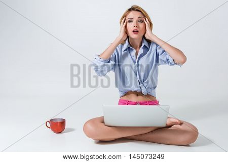 young woman sitting on the floor with crossed legs and using laptop on white background. tired, surprised, tortured, his hands holding his head