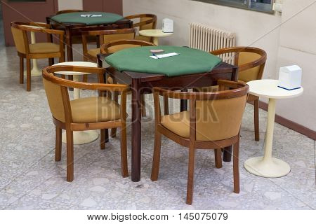 image of tables with green cloth for card games