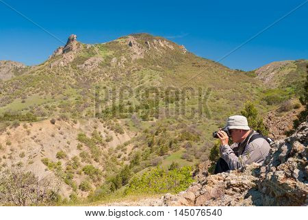 Photographer is taking photos on Kara-dag (extinct volcan) natural reserve Eastern Crimea