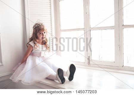 Smiling kid girl princess 5-6 year old wearing stylish white dress and crown sitting on windowsill in room. Looking at camera. Celebrating birthday.