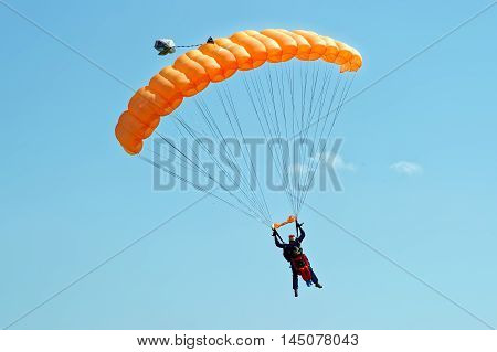 Kharkiv Ukraine - August 20 2016: Skydiver flying on orange parachute at the airfield Korotych Kharkov region Ukraine on August 20 2016