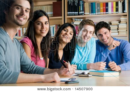 Glücklich Gruppe von jungen Studenten studieren zusammen in einem College-Bibliothek und Blick auf die Kamera zu Lächeln