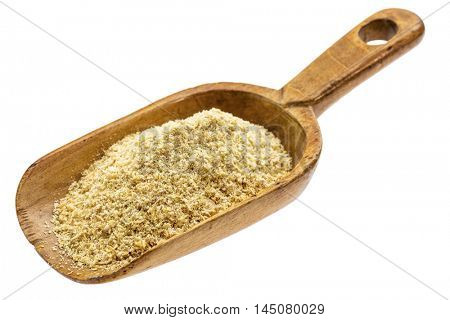 golden flax meal on a rustic wooden scoop, isolated on white