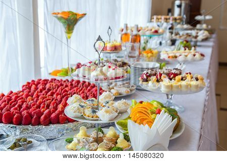 Authentic buffet, assorted fresh fruits, berries and citrus fruits. Morning atmospheric lighting, fashionable trendy spot soft focus. Preparation for design creative menu.