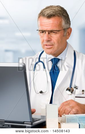 Mature doctor working on laptop and making medication's prescriptions in his clinic office