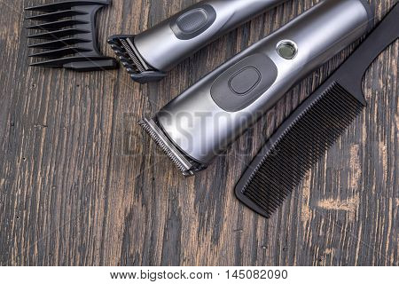Setting with hair clipper and comb on wooden background