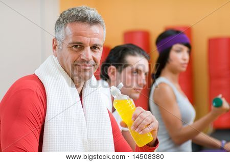 Mature man drinking energy drink during a break at gym