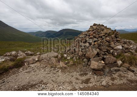 Hill Walkers Approach a Cairn in Scotland
