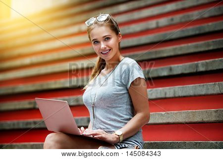 Beautiful student college girl sitting on steps and working on laptop computer. Happy woman with laptop outdoors.