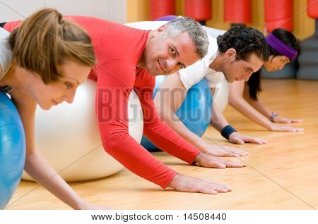 Fitness class lying on front on fitness balls at gym, mature instructor in the centre