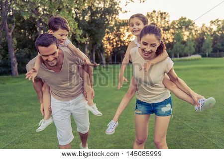 Beautiful happy family is smiling while having fun outdoors kids are sitting pickaback