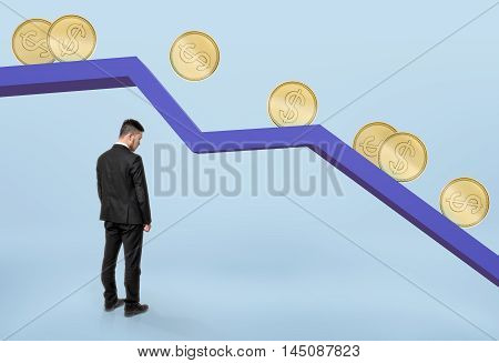 Businessman with his head bowed standing under falling graph with golden coins rolling down. Stock market selloff. Financial market. Economic crisis.