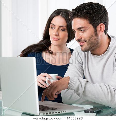 Sonriendo hermosa joven pareja navegando por la red con el ordenador portátil en casa