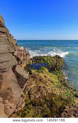 Moss covered rock formation advancing on the sea