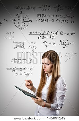 Woman in white is holding pen and documents and solving equation.