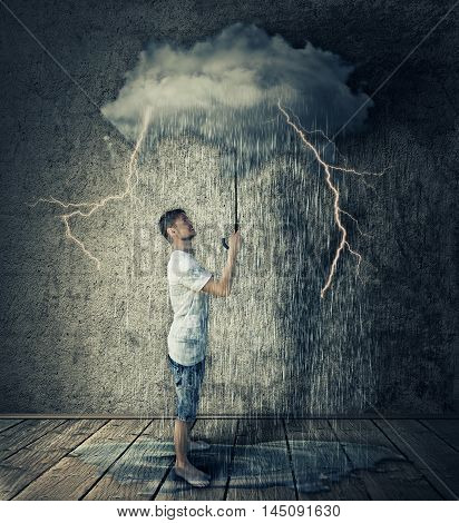 Happy boy stand in a room holding a stormy rainy cloud as umbrella. Business pessimism concept