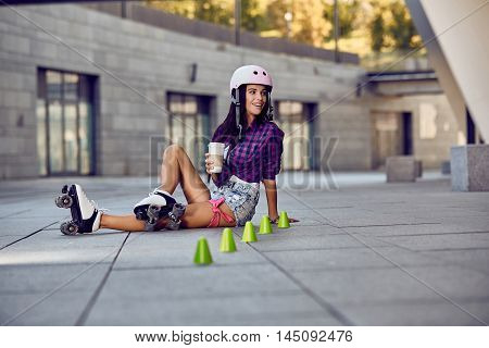 Teenager on rollerblading sitting on street and drink coffee at sunny day. Active lifestyle. Happy young girl enjoying roller skating rollerblading on retro skates sport in urban park.