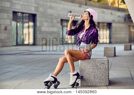 Young woman on roller skates and helmet drinking water. Stylish beautiful girl in shorts and a purple shirt rollerblading. Hipster girl resting after active time in urban skate park.