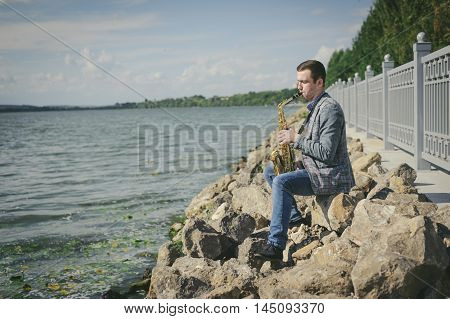 busker playing the saxophone at the railway station and near the fountains