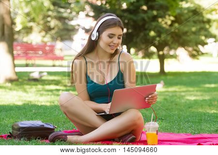 Girl with laptop sits in Park on a blanket listening to music on headphones and using the laptop. Girl on picnic with the laptop and music . She's happy