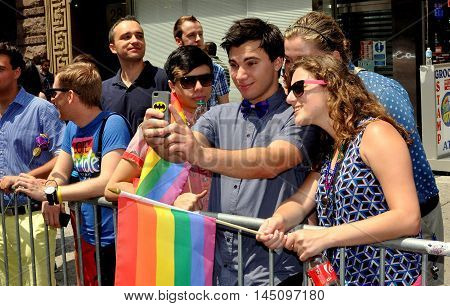 New York City - June 29 2013: Spectators with rainbow flags take a selfie at the 2013 Gay Pride Parade on Fifth Avenue