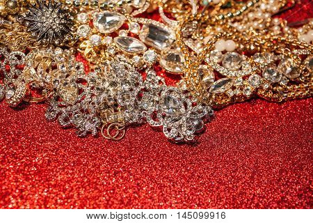Close up of collection of precious jewelry on red shiny glitter background