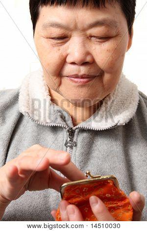 Senior Chinese Woman Taking Money From Bag