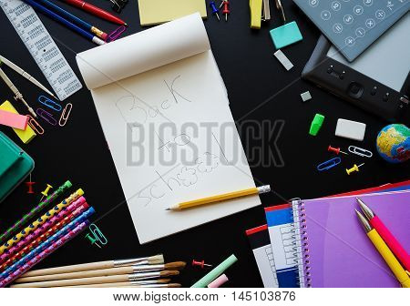 Back to school concept. Notebook with wording Back to school and school supplies with calculator and ebook on blackboard background. Back to school concept with stationery. Top view.