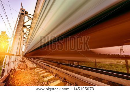 Highspeed train moves fast on the bridge at sunset.