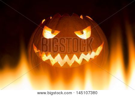 Spooky carved halloween pumpkin in hot burning hell fire flames. The big helloween pumpkin has a mad face with glowing eyes and also a glow in its mouth and teeth. Perspective from bottom up.