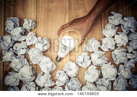 Hand holding a turned on LED light bulb surrounded by crumpled paper ball / Business with new bright ideas and innovation concept