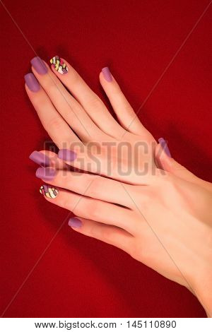 Hands with violet shellac art manicure on red felt background