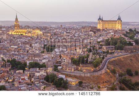Old town cityscape with Alcazar and river Tagus at twilight Toledo Spain