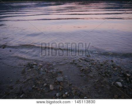 lake shore waves during pinkish purple sunset