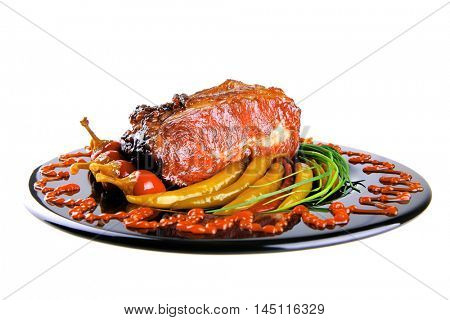 roast red beef meat bbq bloc served on black plate  with green chives red hot pepper on black plate isolated over white background