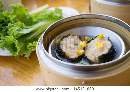 dimsum - steamed pork wrapped with seeweed in bamboo basket on table blur background