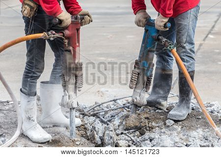 Construction Worker Removes Excess Concrete With Drilling Machine